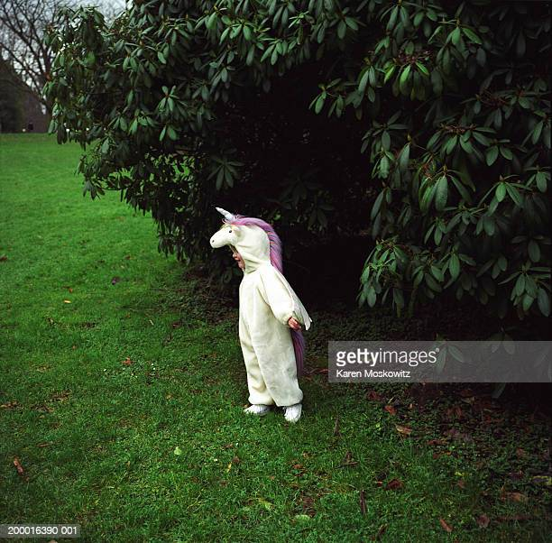 Girl (2-4) wearing unicorn costume in park
