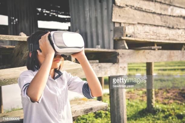 Girl Wearing Virtual Reality Simulator At Field By Log Cabin