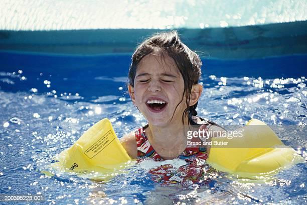 Girl (3-5) wearing water wings in pool