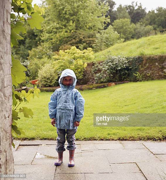 Girl (4-6)  wearing waterproof in garden, smiling, portrtait