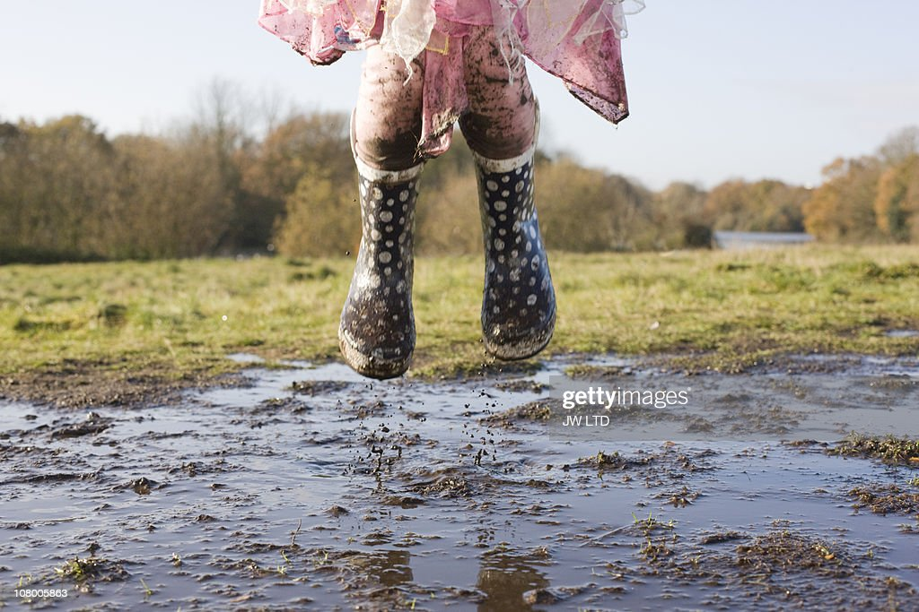 Girl wearing wellington boots jumping in muddy puddle : Stock Photo