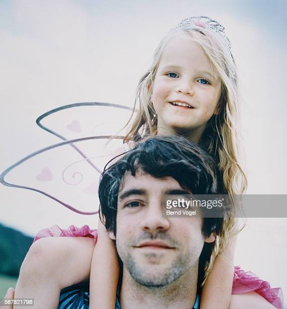 Girl wearing wings and crown, sitting on father's shoulders