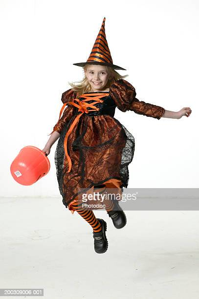 Girl (6-7) wearing witch costume, jumping in studio