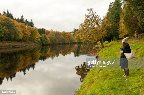 Girl wearing woolly hat stands on river side