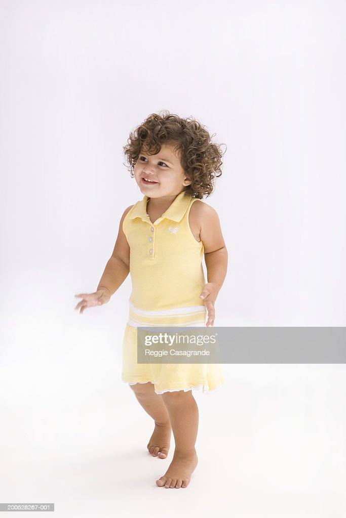 Girl (21-24 months) wearing yellow dress, smiling : Stock Photo