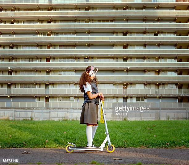 Girl wearing zebra mask riding scooter on housing estate