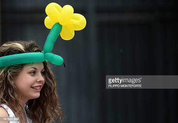 A girl wears a flower shaped ballon hat as she attends a 'workers' day concert' to celebrate Mayday in Rome's Piazza San Giovanni on May 1 2013 AFP...