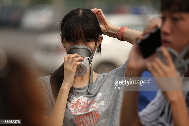 A girl wears a gas mask in a temporary shelter after the explosions in Tianjin on August 14 2015 A Chinese military team of nuclear and chemical...