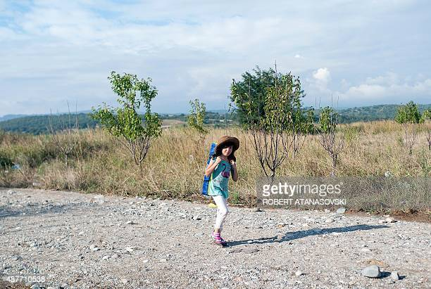 A girl wears a sunhat as she walks with migrants and refugees cross the border line between Greece and Macedonia near the town of Gevgelija on...