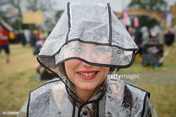 A girl wears a waterproof coat during the first rain showers as revellers gather ahead of the Glastonbury Festival of Music and Performing Arts in...