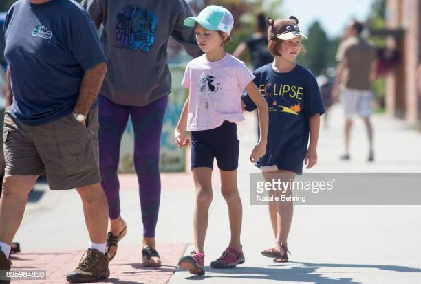 A girl wears an eclipse tshirts as she walks with her family on August 20 2017 in Driggs Idaho The small town expected an influx of more tourists...