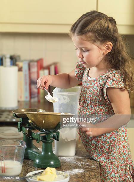 Girl weighing ingredients in kitchen