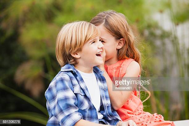 Girl whispering into boys ear