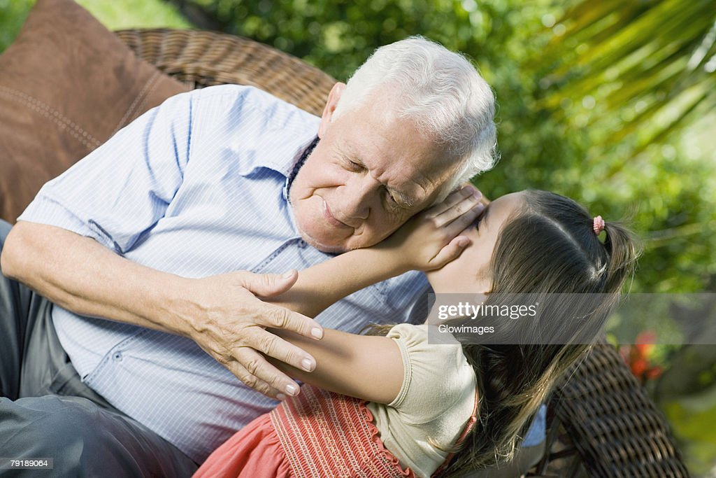 Girl whispering into her grandfather's ear : Foto de stock