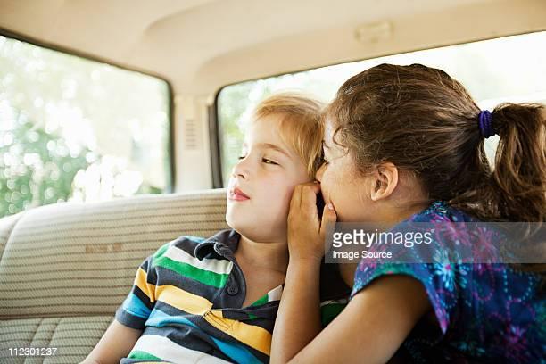 Girl whispering to boy