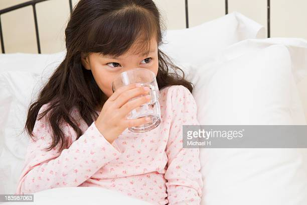 A girl who cared by Grandma is taking pills in bed