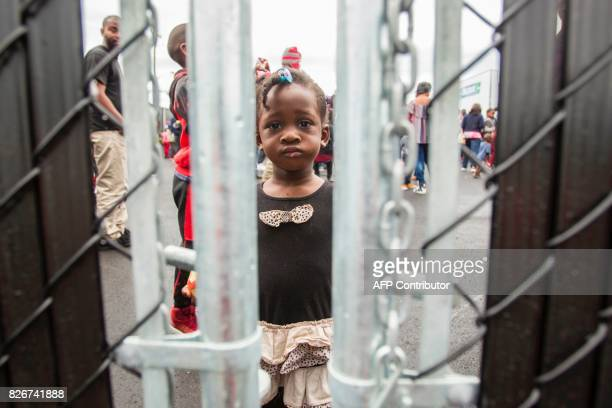 A girl who crossed the Canada/US border illegally with her family claiming refugee status in Canada looks through a fence at a temporary detention...
