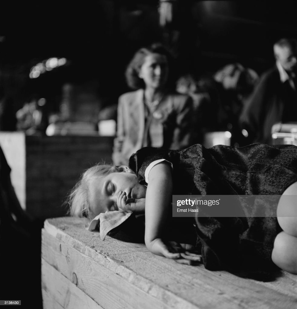 A girl who has just arrived at Ellis Island, on the last boatload of displaced persons (DPs) from WW ll from Europe, curled up asleep on a packing case.