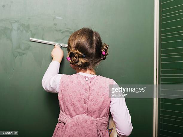 Girl (5-6) wiping blackboard, rear view