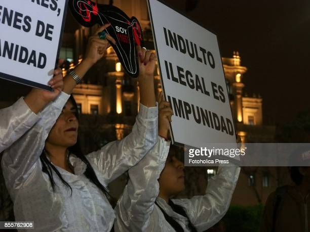 A girl with a banner 'Illegal pardon is impunity' Hundreds of people carrying portraits of their missing relatives took to the streets of Lima in...