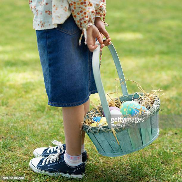 Girl (6-7) with a basket of Easter eggs