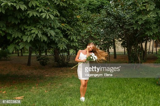 Girl with a bouquet of daisies and flying hair : Stock Photo