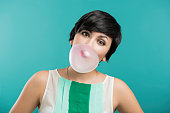Portrait of a beautiful girl with a bubble gum on the mouth, against a blue backgroundPortrait of a beautiful girl with a bubble gum on the mouth, against a blue background