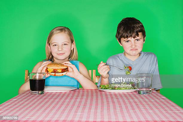 Girl with a burger and boy with a salad