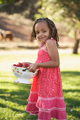 Girl with a colander of strawberries