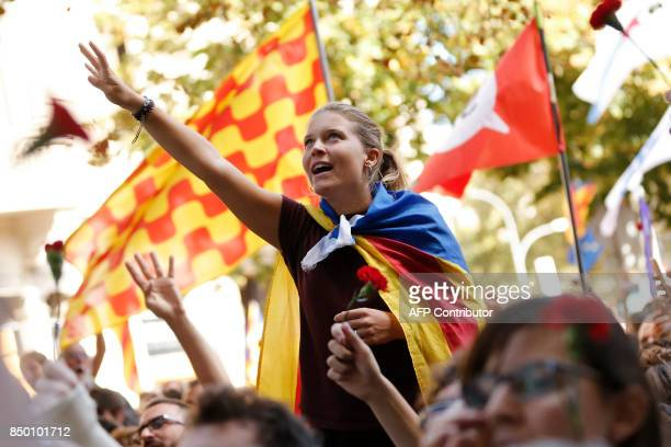 A girl with a 'Estelada' raises his hand as she sings the Catalan anthem during a protest near the Economy headquarters of Catalonia's regional...