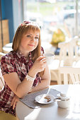 A girl with a European appearance sits in a summer cafe near a large window with a cup of coffee. Vertical photo