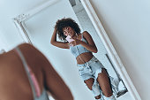 Reflection of beautiful young African woman listening music and keeping hand in hair while taking selfie in the mirror at home