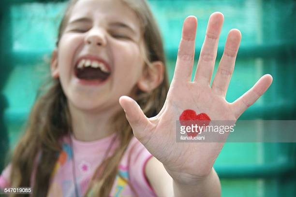 Girl with a heart drawn on the palm of her hand