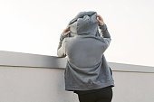 Girl with a hoodie after workout rear view looking at the city