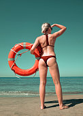 Girl with a lifebuoy on the beach. Lifeguard watching the coastal waters.