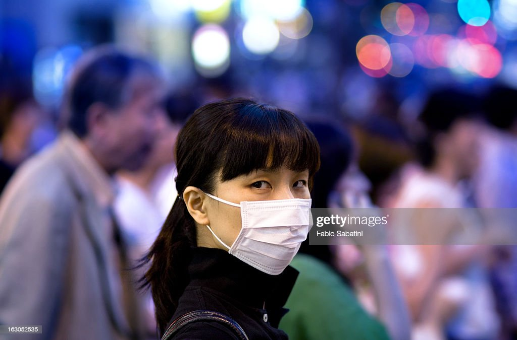 CONTENT] A girl with a mask looks at the camera with intense gaze in Ginza, Tokyo