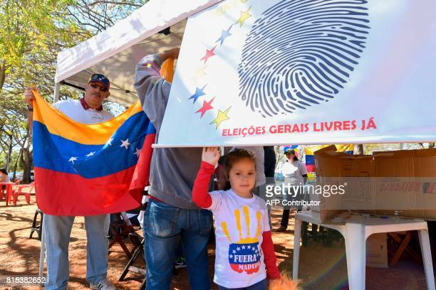 A girl with a Tshirt reading 'Maduro Out' accompanies her mother a Venezuelan living in Brazil during a symbolic plebiscite called by the Venezuelan...