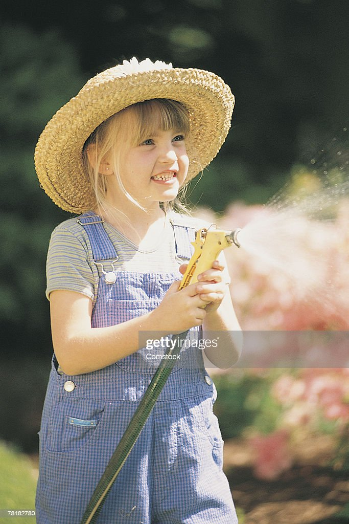 Girl with a water hose : Stock Photo