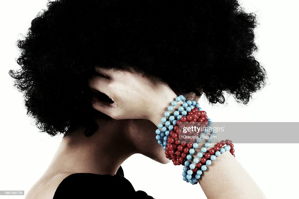 Girl with afro hair holding her head