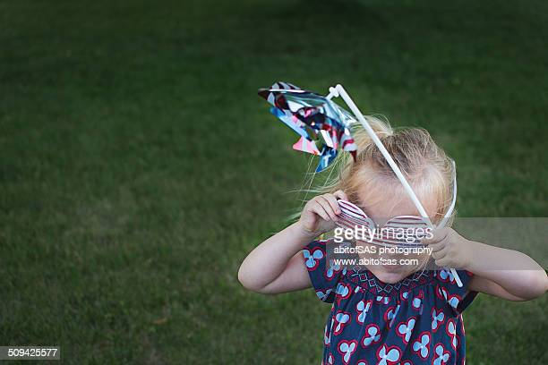 Girl with American flag glasses and flag pinwheel