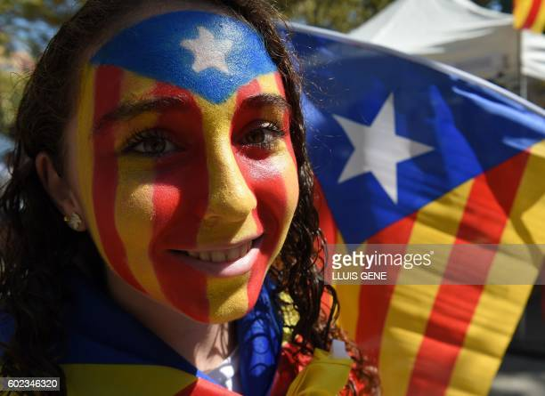 A girl with an Estelada painted on her face smiles before a proindependence demonstration on September 11 in Barcelona during the National Day of...