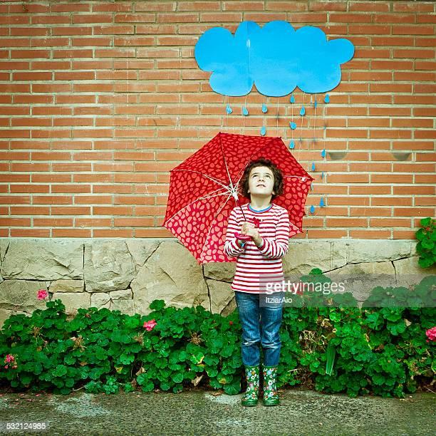 Girl with an umbrella standing under a conceptual rain cloud