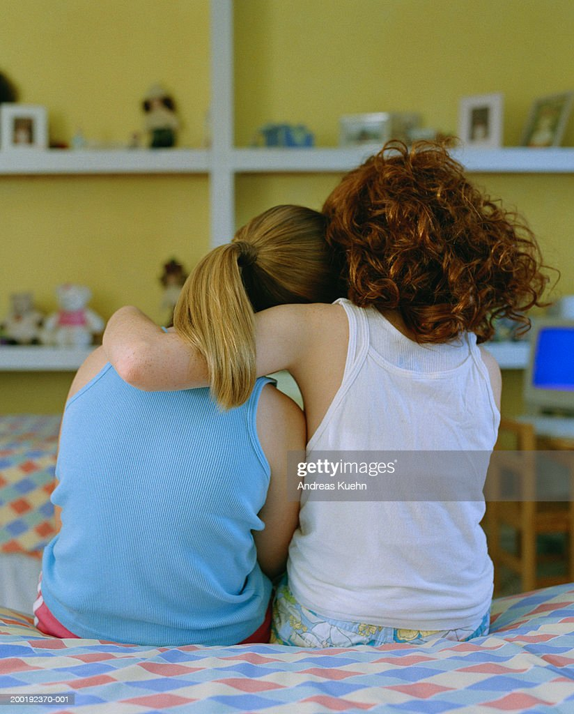 Girl (8-10) with arm around friend, rear view : Stock Photo