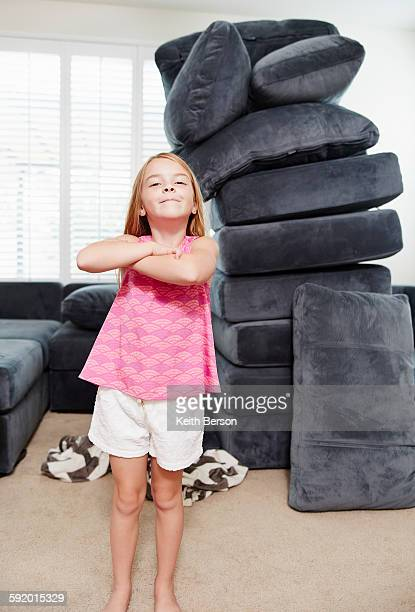 Girl with arms crossed in living room, pile of cushions in background