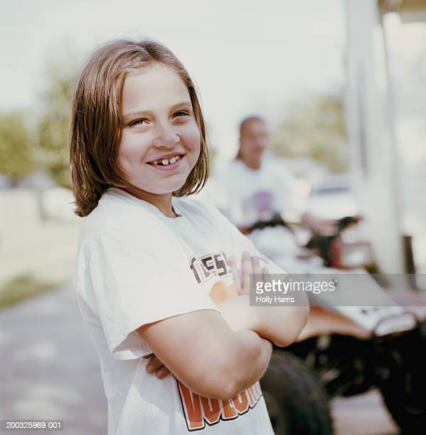 Girl (7-9) with arms crossed, smiling