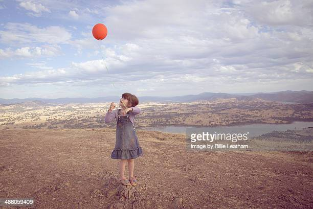 Girl with balloon on hill
