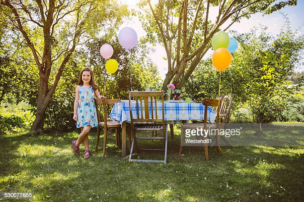 Girl with balloons in garden