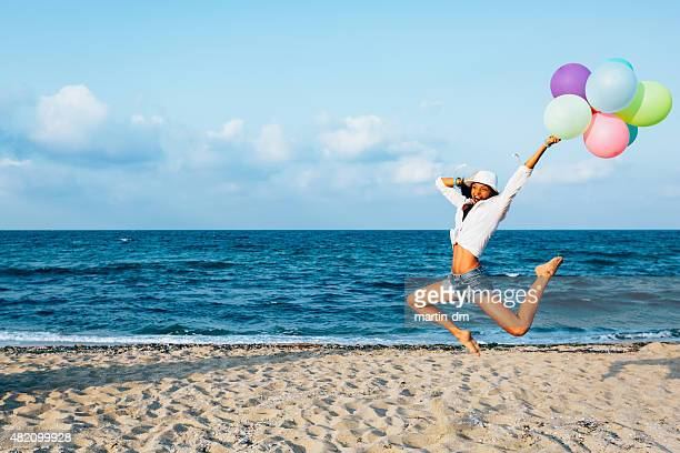 Girl with balloons jumping from joy at the beach