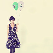 Girl with balloons with number 33 on them