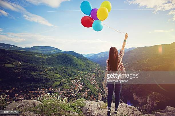 Girl with baloons is standing on the edge